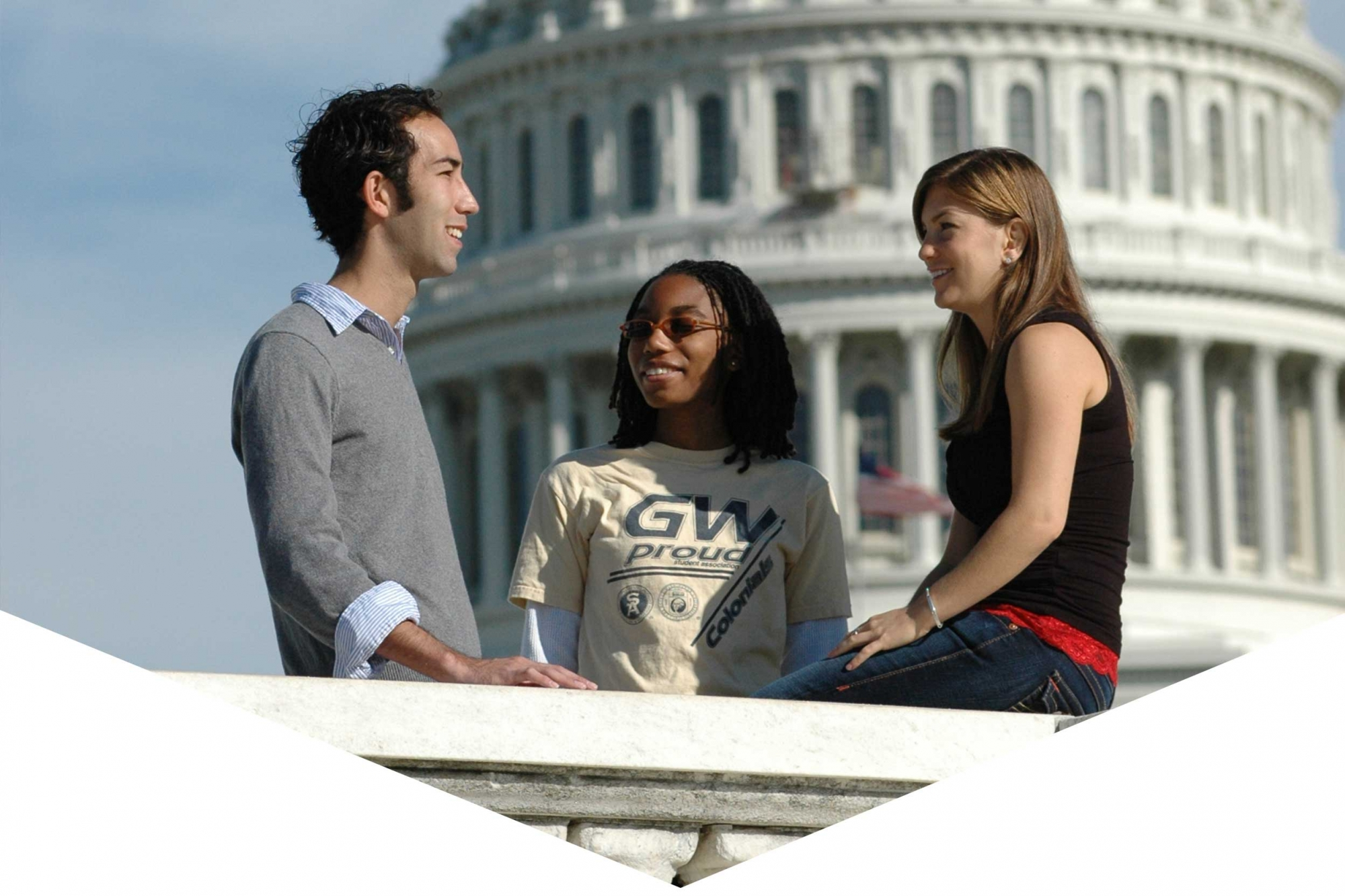 Three students talking with the U.S. Capitol Building in the background